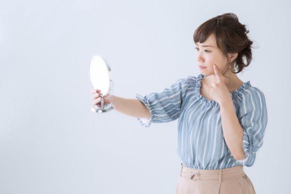 鏡をみてほっぺたを抑える女性